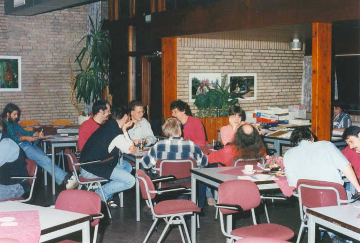 Free evening chat: at left Neven Grbac, at the table in the centre André Knöfel, Marco Langbroek, Sirko Molau, Mirko Nitschke, Detlef Koschny, Manuela Trenn and Axel Haas, at right Danut Ionescu and Visili Micu and in the top right Ina Rendtel and the IMO bookshop (credit Urijan Poerink).