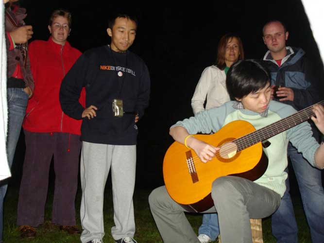 Mengling Zhang playing the guitar at the surprise party at home with Tom Roelandts (credit Jos Nijland).