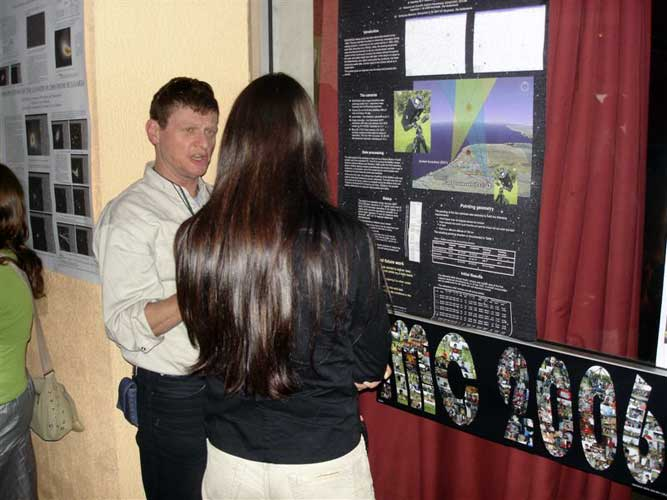 Detlef Koschny during the poster session explaining to Katya Koleva. Notice the large photo mosaic banner of the 2006 IMC made by Galina Ryabova (credit Jos Nijland).