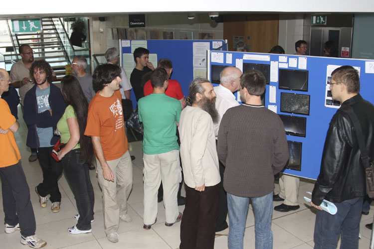 Poster session with from l.to r. Casper ter Kuile (edge), Rafael Barrios, Alex Tudorica, Adriana Nicolae (looking away), Jürgen Rendtel, Adrian Pruna, someone's back, Robert Pomohaci, some backs, Valentin Grigore talking to Javor Kac and Mitja Govedič (credit Bernd Brinkmann).