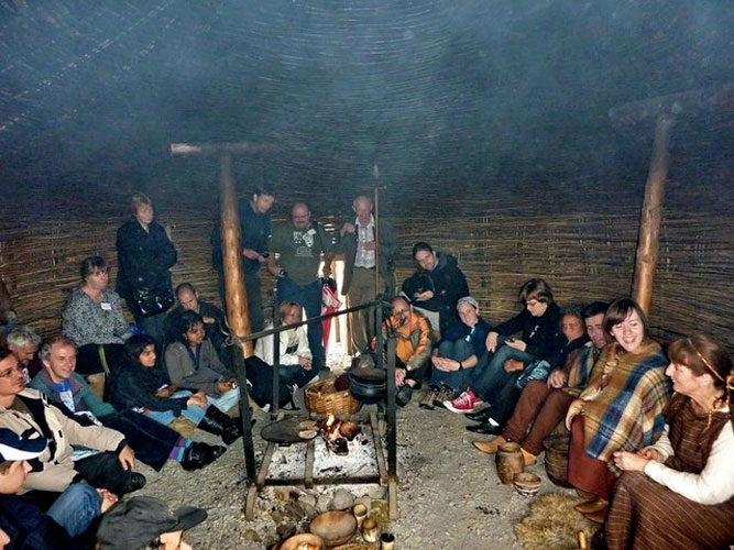 Saturday afternoon visit to Navan Centre: actors perform the daily life of the Navan tribes, cosy around the fire going from right to left Antonio Martinez Picar, Chris Trayner, Tony Markham, Bernadette Foley, Naslim Neelamkodan, Elise Ijland, Kamalam Vanninathan, Arnold Tukkers, Jos Nijland, Anna Kartashova, William Cooke, Terry Moseley, Christian Steyaert, Luc Bastiaens, Megan Argo, Geert Barentsen, Eliška Anna Kubičková and three 'Navans' (credit Valentin Grigore).