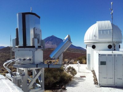 Figure 1. AMOS system along with the new spectral camera (right) on Teide Observatory, IAC. The Teide Volcano of Tenerife can be seen in the background, and the cupola of the SONG telescope is on the far right. (Author: J. Šimon)