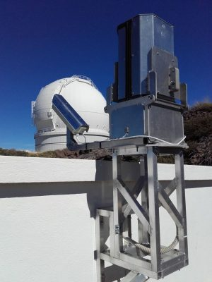 Figure 2. AMOS system along with the new spectral camera (left) on Roche de Los Muchachos Observatory, IAC. The cupola of the 4 meter Herschel telescope can be seen in the background. (Author: J. Šimon)